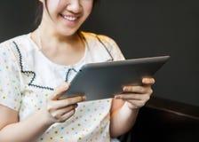 Lycklig kvinna som använder minnestavlaPC Royaltyfri Foto