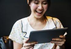 Lycklig kvinna som använder minnestavlaPC Arkivbild