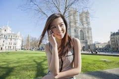 Lycklig kvinna som använder mobiltelefonen mot den Westminster abbotskloster i London, England, UK Royaltyfri Foto
