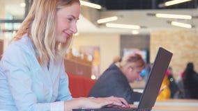 Lycklig kvinna som använder skype på bärbara datorn stock video