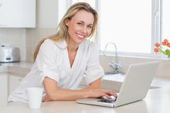 Lycklig kvinna som använder bärbara datorn på räknaren Arkivbilder