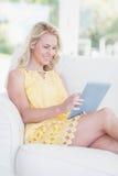 Lycklig kvinna som använder minnestavlan på soffan Royaltyfri Bild
