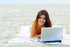Lycklig kvinna som arbetar på bärbara datorn, medan ligga på stranden Arkivfoto