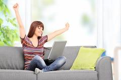 Lycklig kvinna som arbetar på bärbara datorn och gör en gest lycka Arkivbild