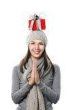 Lycklig kvinna som balanserar en julgåva på hennes huvud Royaltyfria Bilder