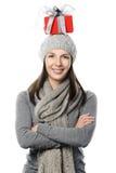 Lycklig kvinna som balanserar en julgåva på hennes huvud Arkivbild