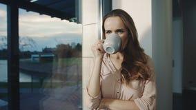 Lycklig kvinna som blir nära fönster efter arbetsdags Kopplade av kvinnan som den har, vilar stock video