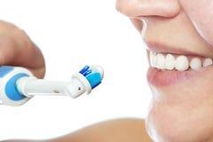 Lycklig kvinna som borstar den elektriska tandborsten för tänder med tandkräm Royaltyfri Foto