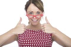 Lycklig kvinna som bär röda inramade exponeringsglas med tummar upp Arkivbild