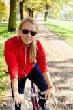 Lycklig kvinna som cirkulerar på cykeln, höst Arkivbild