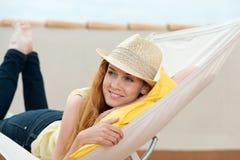 Lycklig kvinna som dagdrömmer i hängmatta royaltyfria foton