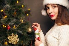 Lycklig kvinna som dekorerar ett julträd royaltyfri fotografi