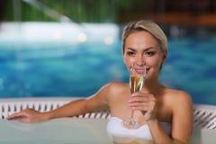 Lycklig kvinna som dricker champagne på simbassängen Arkivfoton