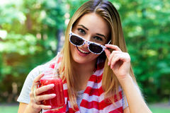 Lycklig kvinna som dricker en smoothie utanför på 4th Juli Royaltyfria Foton