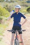 Lycklig kvinna som dricker, når att ha cyklat Royaltyfri Fotografi