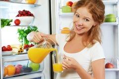 Lycklig kvinna som dricker orange fruktsaft om kylskåpet Royaltyfria Bilder