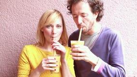 Lycklig kvinna som dricker smoothien med sugrör lager videofilmer