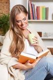 Lycklig kvinna som dricker te, medan läsa Fotografering för Bildbyråer