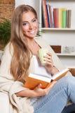 Lycklig kvinna som dricker te, medan läsa Arkivbilder