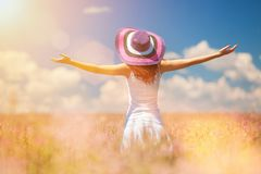 Lycklig kvinna som enjoing livet i fältet med blommor arkivfoton