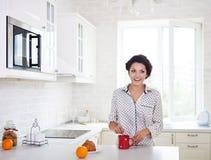 Lycklig kvinna som förbereder en kopp kaffe i hennes kök Arkivfoto