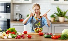 Lycklig kvinna som förbereder grönsaksallad i kök royaltyfri foto