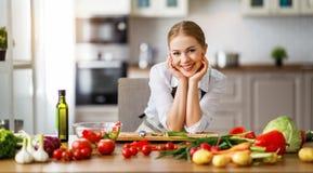 Lycklig kvinna som f?rbereder gr?nsaksallad i k?k royaltyfri foto