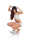 Lycklig kvinna som firar hennes nya vikt på en skala Royaltyfria Foton