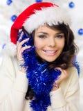 Lycklig kvinna som firar jul i en jultomtenhatt Arkivbild