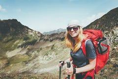 Lycklig kvinna som fotvandrar med ryggsäcken på berg royaltyfri bild