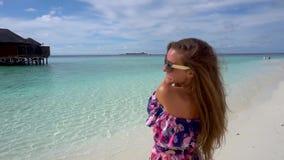 Lycklig kvinna som går, le och havnggyckel på havstranden av Maldiverna arkivfilmer