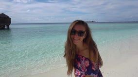 Lycklig kvinna som går, le och havnggyckel på havstranden av Maldiverna lager videofilmer