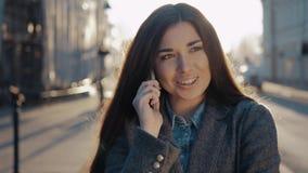 Lycklig kvinna som går och använder en smart telefon på gatan i autumm på solnedgång Sexig studentflicka med den mobila smartphon arkivfilmer