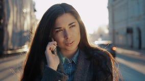 Lycklig kvinna som går och använder en smart telefon på gatan i autumm på solnedgång Sexig studentflicka med den mobila smartphon lager videofilmer
