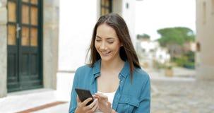 Lycklig kvinna som går och bläddrar mobiltelefonen i gatan