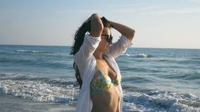 Lycklig kvinna som går och rotera på havsstranden på den soliga dagen Ung le flicka i solglasögon som spelar med hennes hår och lager videofilmer