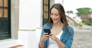Lycklig kvinna som går och smsar på mobiltelefonen i en gata