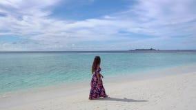 Lycklig kvinna som går på stranden nära havet i Maldiverna arkivfilmer