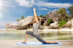 Lycklig kvinna som gör yoga i lågt utfall på stranden Fotografering för Bildbyråer
