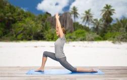 Lycklig kvinna som gör yoga i lågt utfall på stranden Royaltyfri Bild