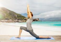 Lycklig kvinna som gör yoga i lågt utfall på stranden Royaltyfria Foton