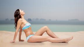 Lycklig kvinna som garvar i bikini över simbassäng Arkivfoton