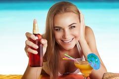 Lycklig kvinna som garvar på stranden royaltyfria foton