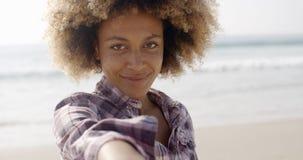 Lycklig kvinna som ger handen på stranden Royaltyfria Bilder