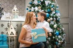Lycklig kvinna som ger julklapp till hennes son Arkivbild