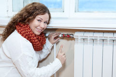 Lycklig kvinna som gör en gest, när kontrollera termostaten på centralvärmeelementet Arkivfoton