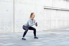 Lycklig kvinna som gör squats och utomhus övar Arkivbild
