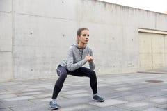 Lycklig kvinna som gör squats och utomhus övar Arkivbilder