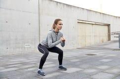 Lycklig kvinna som gör squats och utomhus övar Royaltyfri Foto