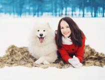 Lycklig kvinna som har gyckel med den vita Samoyedhunden utomhus på den insnöade vinterdagen Royaltyfri Bild